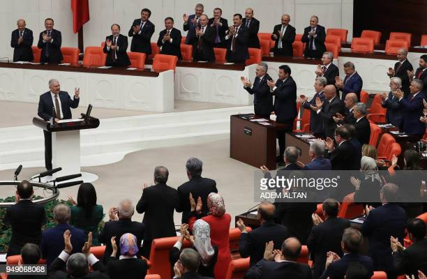 TOPSHOT Members of Parliament applaud as Turkish Prime Minister Binali Yildirim speaks during the debate motion on proposed early presidential and...