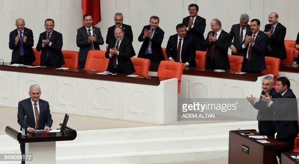 Members of Parliament applaud as Turkish Prime Minister Binali Yildirim speaks during the debate motion on proposed early presidential and...