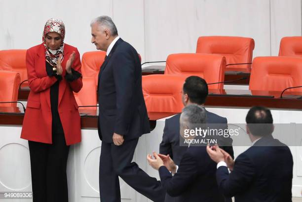 Members of Parliament applaud as Turkish Prime Minister Binali Yildirim arrives to speak during the debate motion on proposed early presidential and...