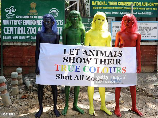 Members of 'People for the Ethical Treatment of Animals' painted in various colours stand behind a banner that read Let Animals show their true...