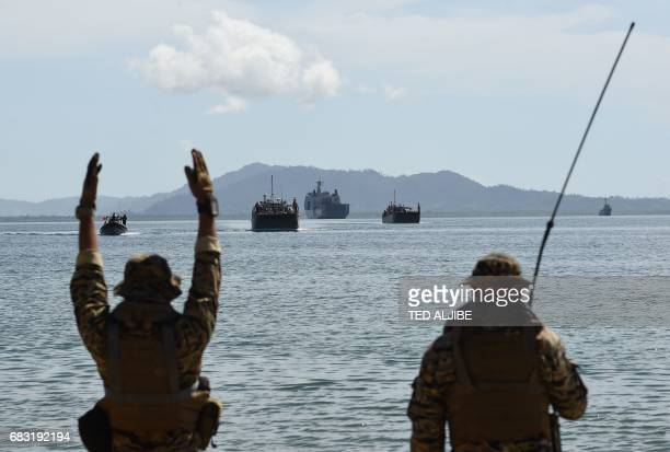 Members of Philippine navy special operations group signal to Philippine landing ships loaded with PhilippineUS marines and civilian volunteers as...