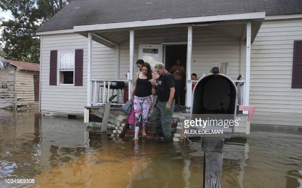 Members of police and North Carolina National Guard assist a woman eight months pregnant in Lumberton North Carolina on September 17 2018...