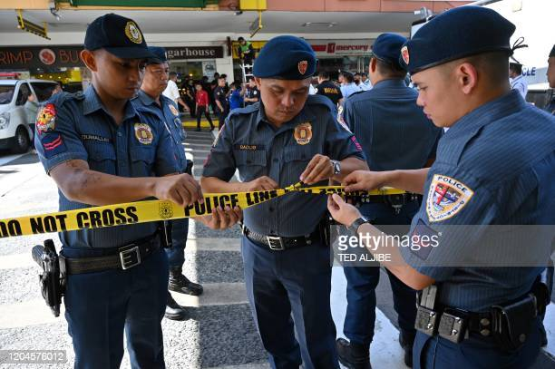 Members of police cordon off the area outside a mall after a hostage situation was reported in suburban Manila on March 2, 2020. - Heavily armed...