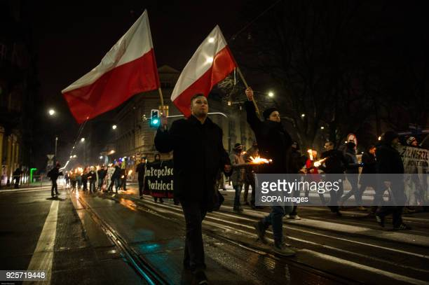 Members of polish conservative right wing movement seen holding Polish flags as they attend a silent march for the National Day of Remembrance of the...