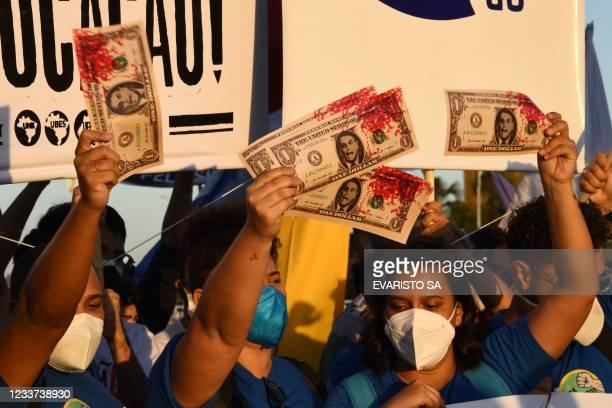 Members of political parties and civil society organizations hold fake dollar bills depicting Brazilian Presidnet Jair Bolsonaro's face and tinted in...