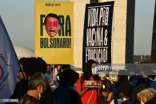 Members of political parties and civil society organizations hold signs reading Bolsonaro out and Life, bread, vaccine and education during a protest...