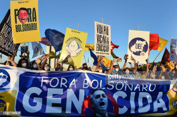 Members of political parties and civil society organizations protest with a banner reading Bolsonaro out, genocide outside the National Congress in...