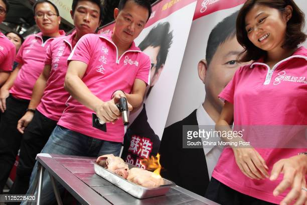 Members of Power Voters including Ray Chan Chi-chuen and Erica Yuen Mi-ming burn a baby pigeon with a gas torch outside the Democratic Party's...