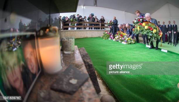 Members of public life in the region place wreaths at the collective grave in the cemetery following the memorial service for the victims of the...