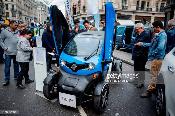 Members of public look at a Renault Twizy electric vehicle during the Regent Street Motor Show in London on November 4 2017 A driverless electric car...