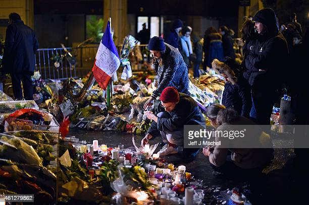 Members of public the light candles in tribute near the offices of French satirical magazine Charlie Hebdo on January 10, 2015 in Paris, France. Four...