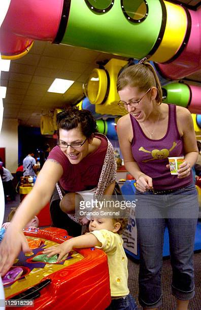 Members of 'punkymoms' Rebecca Rawson left and Angie Ross play a game with Rebecca's daughter Josie at the Chuck E Cheese in Altamonte Springs...
