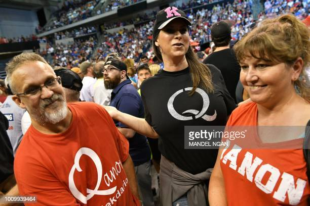 Members of QAnon await the arrival of US President Donald Trump for a political rally at Mohegan Sun Arena in WilkesBarre Pennsylvania on August 2...