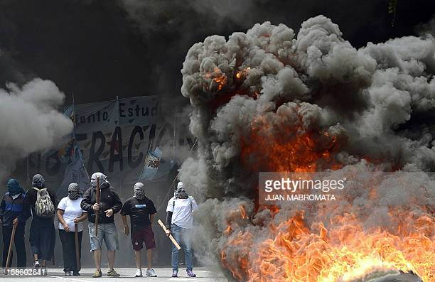 Members of Quebracho organization burn tires whie blocking 9 de Julio avenue on December 20 2012 in Buenos Aires during a demonstration on the 11th...