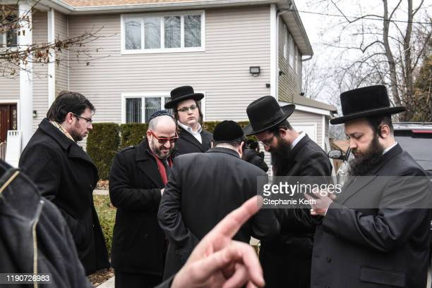 Members of Rabbi Chaim Rottenberg's community gather in front of the house of Rabbi Chaim Rottenberg on December 29 2019 in Monsey New York Five...