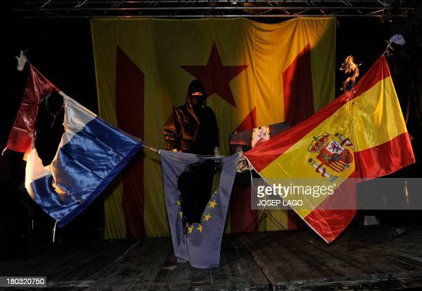 Members of radical left-wing Catalan independentist political party CUP set fire to French, European and Spanish flags during Catalonia National Day,...