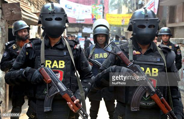 Members of Rapid Action Battalion stand guard outside the militant hideout on January 12 2018 in Dhaka Bangladesh Three militants have been killed...