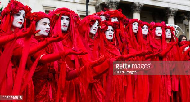 Members of Red Brigade from Extinction Rebellion movement in their costumes protesting on the steps of Trafalgar Square during the third day of their...