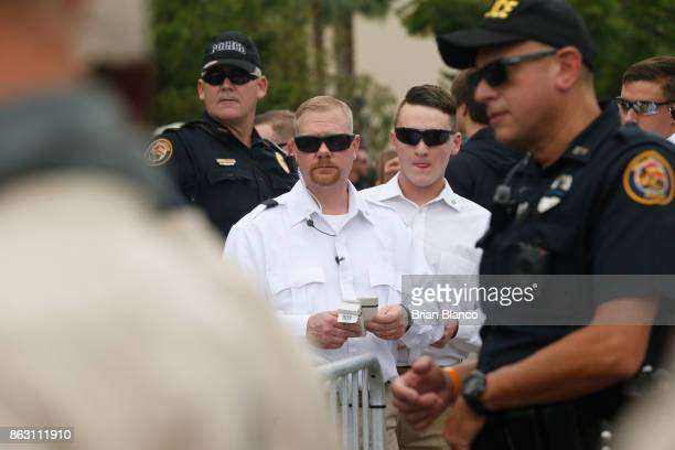 Members of Richard Spencer's security team in white stand behind police and decide who gets tickets to a speech by white nationalist Richard Spencer...
