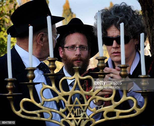 Members of Romanian Jewish comunity among them Romanian actress Maia Morgenstern light candles during a religious service at a Jewish cemetery...