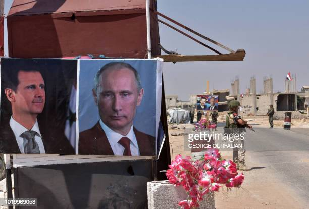 Members of Russian and Syrian forces stand guard near posters of Syrian President Bashar alAssad and his Russian counterpart Vladimir Putin at the...