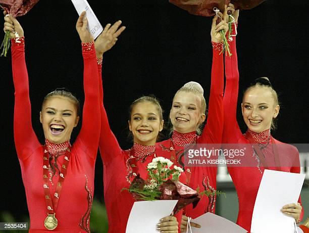 Members of Russian national team Irina Tchachina Alina Kabaeva Olga Kapranova and Vera Sessina wave on podium as they celebrate their gold medal in...