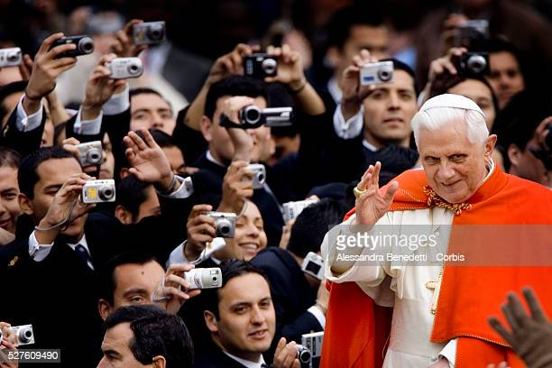 Members of Santiago del Chile police officers school take pictures of Pope Benedict XVI as he arrives in St Peter's Square to preside over his...