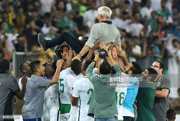 Members of Saudi Arabia's football team carry head coach Bert van Marwijk as they celebrate at the end of the FIFA World Cup 2018 qualification...