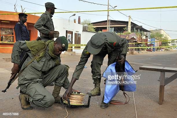 Members of security forces work near La Terrasse restaurant in Bamako on March 7 after five people including a French and a Belgian national were...