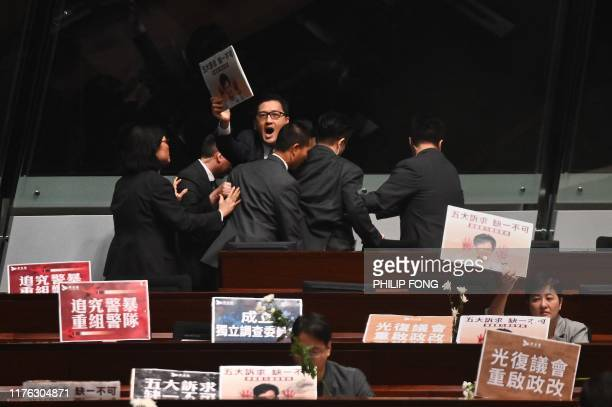 TOPSHOT Members of security try to block prodemocracy lawmaker Lam Cheukting as he chants slogans in protest as Hong Kong Chief Executive Carrie Lam...