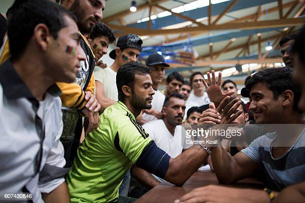 Members of several cricket teams from across eastern Germany enjoy arm wrestling during a regional tournament on September 17 2016 in Bischofswerda...