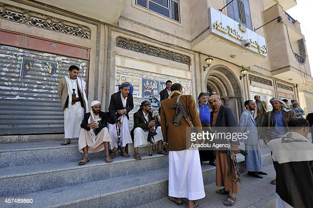 Members of Shia Houthi Ansarullah movement stand guard after capturing governor's building in Sana'a Yemen on October 19 2014