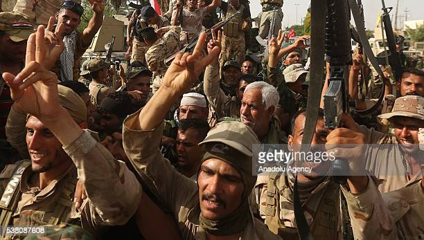 Members of Shiite Hasdi Sabi make victory sign after they recaptured Fallujah's Saklaviye district from Daesh in Anbar Iraq on June 04 2016