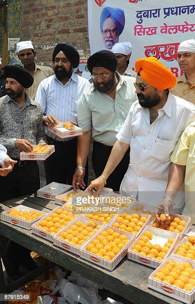 Members of Sikhs Welfare Society distribute sweets to celebrate the second term of Prime Ministership for Manmohan Singh at Gurudwara Racab Ganj in...