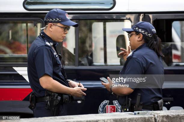 Members of Singapore Police Force stand on duty outside the St Regis Hotel on June 11 2018 in Singapore The historic meeting between US President...