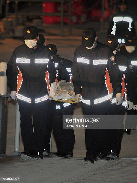 Members of South Korean rescue team carry the body of a passenger retrieved from a capsized ferry at a harbour in Jindo on April 19 2014...