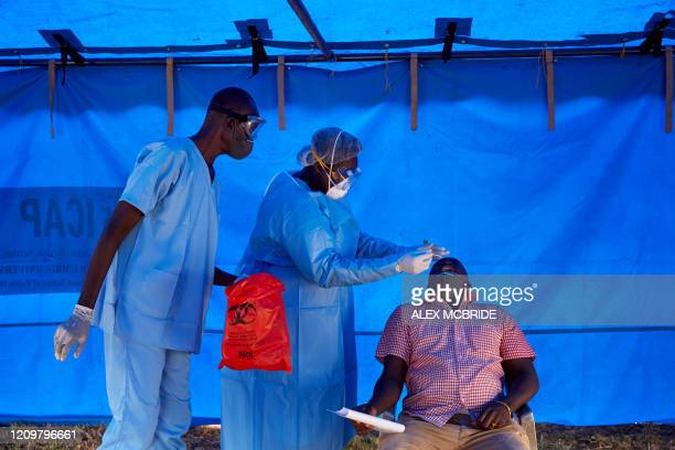Members of South Sudanese Ministry of Health's Rapid Response Team take a sample from a man who has recently been in contact with a confirmed case of...