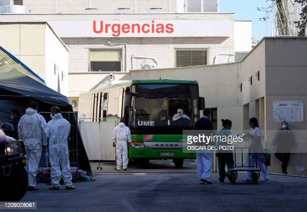 Members of Spanish Military Emergencies Unit wearing protective suits stand outside a bus used to transport patients from the Gregorio Maranon...