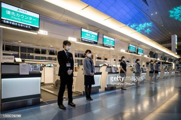 Members of Spring Airlines ground staff stand in front of the checkin counter at Haneda airport on January 31 2020 in Tokyo Japan The Chinese...