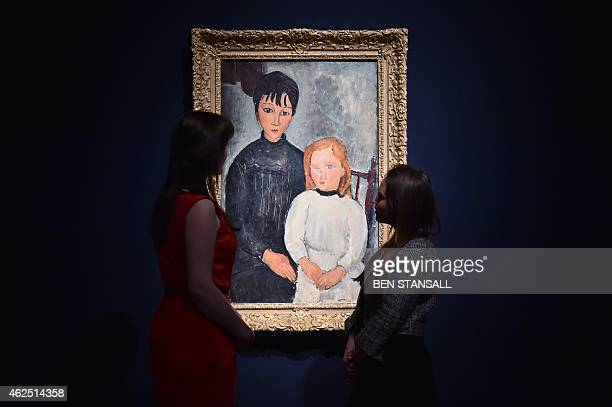 Members of staff look at a work of art by Amedeo Modigliani entitled 'Les deux filles' which is estimatd to fetch 68 million British pounds during...