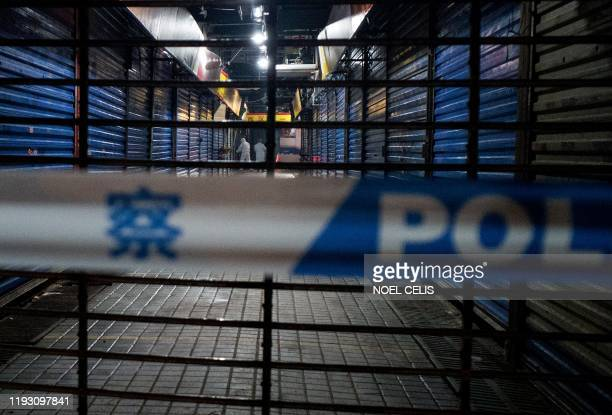 Members of staff of the Wuhan Hygiene Emergency Response Team conduct searches on the closed Huanan Seafood Wholesale Market in the city of Wuhan in...