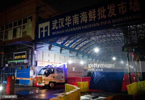 Members of staff of the Wuhan Hygiene Emergency Response Team drive their vehicle as they leave the closed Huanan Seafood Wholesale Market in the...