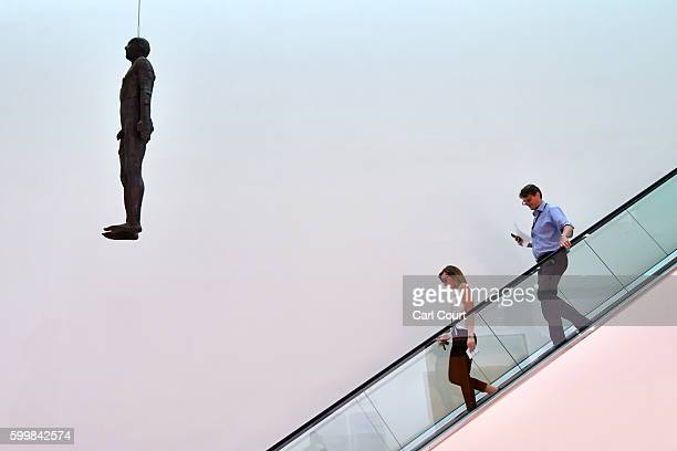 Members of staff pass by an artwork by British artist Antony Gormley entitled 'Object 199' a lifesize castiron sculpture cast from the artist's body...