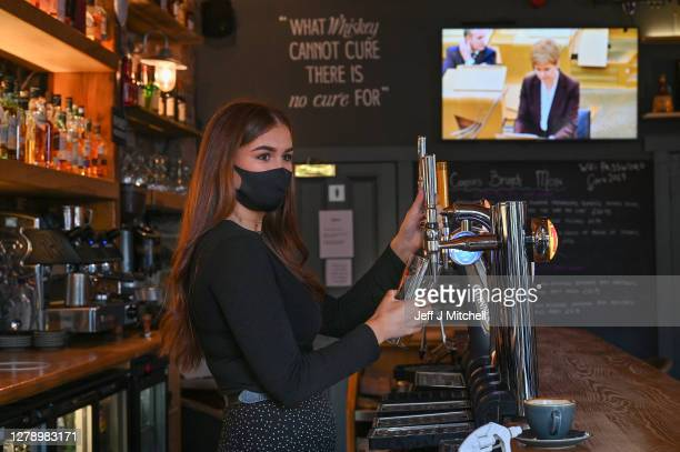 Members of staff serves a pint as customers watch an announcement by Nicola Sturgeon at O'Connors on October 7, 2020 in Edinburgh, Scotland. New...