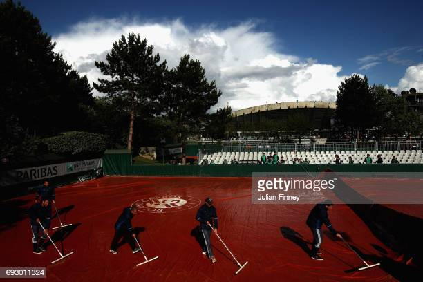 Members of staff sweep the outside courts following a rain delay on day ten of the 2017 French Open at Roland Garros on June 6 2017 in Paris France