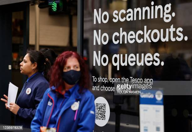 Members of staff wait to help customers arriving at supermarket chain Tesco's first check-out free food store in Holborn, central London, on October...