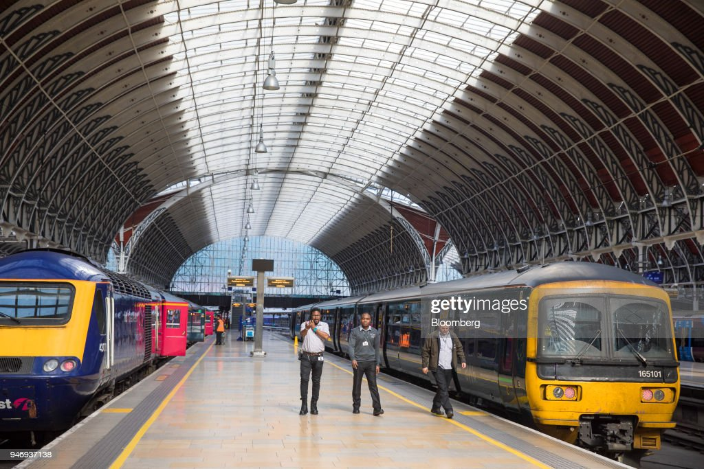 Members of staff walk along a platform past First Great Western trains, operated by FirstGroup Plc, at London Paddington railway station in London, U.K., on Monday, April 16, 2018. British train and bus operator FirstGroup Plc said it rejected an 'opportunistic' takeover proposal that private-equity firm Apollo Management made as the company struggles with under-performing rail routes in the U.K. and competition from discount airlines in the U.S. Photographer: Jason Alden/Bloomberg via Getty Images