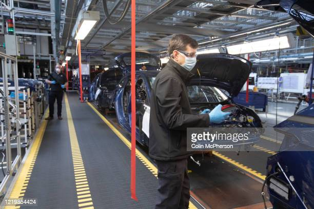 Members of staff working between two-metre wide designated work stations on a car assembly line at the Vauxhall car factory during preparedness tests...