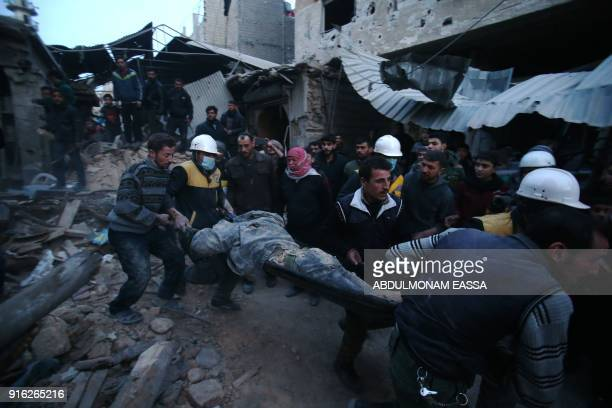 TOPSHOT Members of Syrian civil defence forces known as the White Helmets evacuate a victim of an air strike in the rebelheld enclave of Arbin in the...