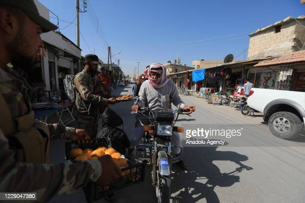 Members of Syrian National Army offer fruit and cookies to people during an event to mark the first year of Operation Peace Spring as life turned to...